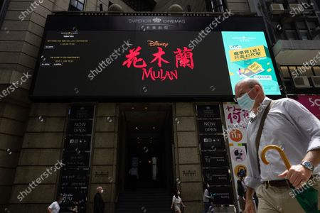 "People walk past a huge TV screen showing movie ""Mulan"" at a downtown street in Hong Kong . The remake of ""Mulan"" struck all the right chords to be a hit in the key Chinese market. Disney cast beloved actresses Liu Yifei as Mulan and removed a popular dragon sidekick in the original to cater to Chinese tastes"