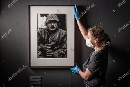 Stock Picture of Don Mccullin Retrospective at the Tate in Liverpool - Final touches to the exhibition by team Janeny Hunetr and Danny John. Two of his famous photos including the Shell Shocked US Marine and the Homeless Man in East London and One of His Somber Landscape