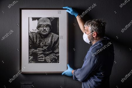 Don Mccullin Retrospective at the Tate in Liverpool - Final touches to the exhibition by team Janeny Hunetr and Danny John. Two of his famous photos including the Shell Shocked US Marine and the Homeless Man in East London and One of His Somber Landscape