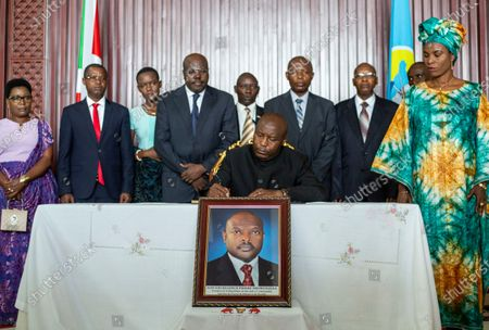 """Burundi's president-elect Evariste Ndayishimiye, center, accompanied by his wife Angeline Ndayubaha, right, signs the book of condolences, above a photograph of the late President Pierre Nkurunziza, at the presidential palace in Bujumbura, Burundi. A new report released Thursday, Sept. 17, 2020 by the United Nations commission of inquiry on Burundi sees little optimism in the government of new President Evariste Ndayishimiye, saying it is """"extremely concerned"""" that he has appointed senior officials who face international sanctions for alleged human rights abuses in the country's 2015 political turmoil"""