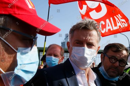 Communist party parliament member Fabien Roussel, center, and Bridgestone employees gather outside the tire factory of Bethune, northern France, Thursday, Sept.17, 2020. Workers protest over the Japan-based company's decision to close the plant and lay off all its nearly 900 workers. Bridgestone argues the factory is no longer competitive globally, but unions and French politicians accused the company of using the virus-driven economic crisis as a pretext for the closure and not investing in modernizing the plant instead