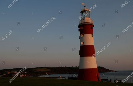 Stock Picture of Smeaton's Tower, a memorial to celebrated civil engineer John Smeaton, on the Hoe in Plymouth south west England, . The Mayflower sailed from Plymouth for the Americas on 16th September 1620, 400 years ago. The city boasts the largest operational naval base in Europe. In the background is an art work created by a local artist collective Still/Moving, 'Speedwell' an art work made up of LED lights