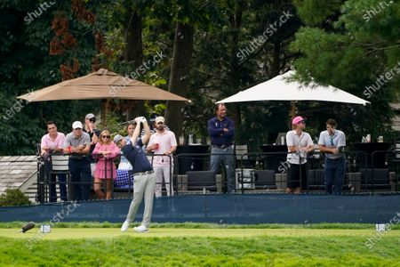 Spectators watch from the backyard of a home overlooking the course as Branden Grace, of South Africa, plays his shot from the 11th tee during the first round of the US Open Golf Championship, in Mamaroneck, N.Y