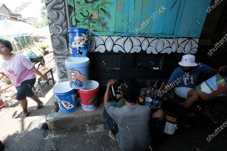 A craftsmen painting a washing place using plastic waste from paint buckets. Recycling plastic waste as a way to preserve the environment.