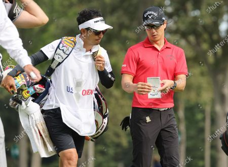 Ryo Ishikawa of Japan (R) and his caddie Go Tanaka (L) talk as they walk off the tee on the eighth hole during the first round of the 2020 US Open at Winged Foot Golf Club in Mamaroneck, New York, USA, 17 September 2020. The 2020 US Open will be played from 17 September through 20 September in front of no fans due to the ongoing coronovirus pandemic.