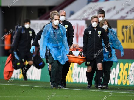 Burnley's Johann Berg Gudmundsson is carried off the pitch on a stretcher after picking up an injury during the English League Cup soccer match between Burnley and Sheffield United at the Turf Moor stadium in Burnley, England