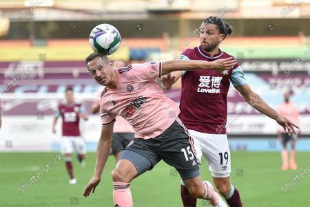 Sheffield United's Phil Jagielka, left, duels for the ball with Burnley's Jay Rodriguez during the English League Cup soccer match between Burnley and Sheffield United at the Turf Moor stadium in Burnley, England