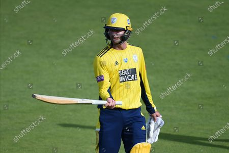 Ian Holland of Hampshire replays his shot as he is dismissed by Reece Topley