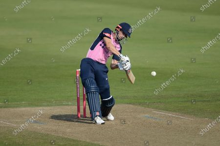 John Simpson of Middlesex hits the ball over the boundary for 6 runs