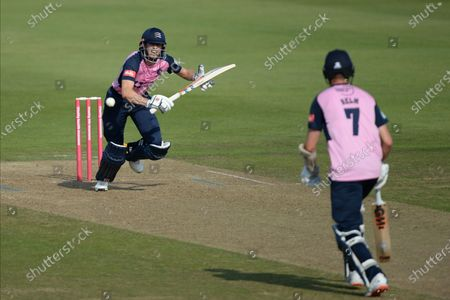 John Simpson (left) and Tom Helm of Middlesex run a single off the bowling of Ryan Stevenson