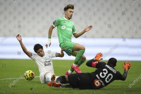 Saint-Etienne's Adil Aouchiche, center, fights for the ball with Marseille's goalkeeper Steve Mandanda, right, and Marseille's Hiroki Sakai during the French League One soccer match between Marseille and Saint Etienne at the Stade Velodrome in Marseille, France, Thursday, Sept.17, 2020