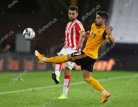 Stoke City's Tommy Smith, left, shoots the ball as Wolverhampton Wanderers' Romain Saiss tries to stop him, during the English League Cup soccer match between Wolverhampton Wanderers and Stoke City, in Molineux Stadium in Wolverhampton, England