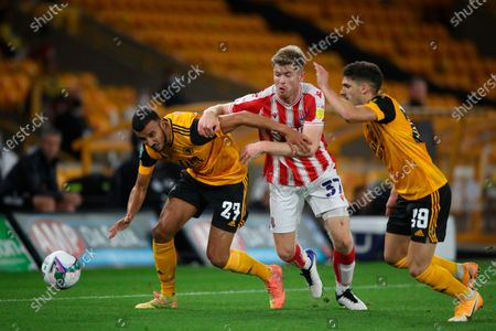 Wolverhampton Wanderers' Romain Saiss, left tries to dribble past Stoke City's Nathan Collins, centre, as Wolverhampton Wanderers' right, looks on during the English League Cup soccer match between Wolverhampton Wanderers and Stoke City, in Molineux Stadium in Wolverhampton, England