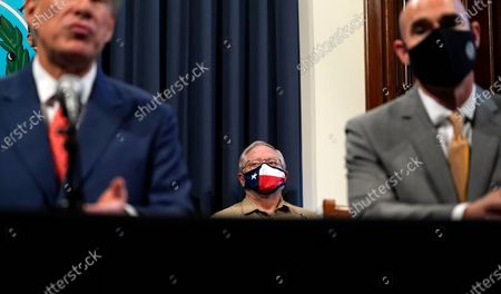 Texas Department of State Health Services Commissioner Dr. John Hellerstedt, center, listens to Texas Gov. Greg Abbott speaks during a news conference where he provided an update to Texas' response to COVID-19, in Austin, Texas
