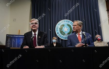 Texas Gov. Greg Abbott, right, listens to Lt. Governor Dan Patrick, left, during a news conference where they provided an update to Texas' response to COVID-19, in Austin, Texas