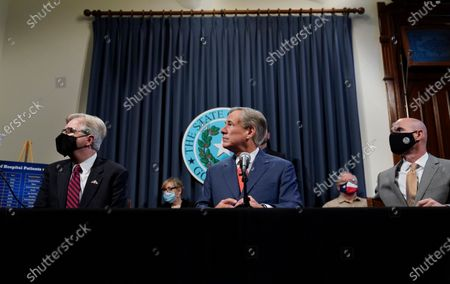 Lt. Governor Dan Patrick, left, Texas Gov. Greg Abbott, and Speaker Dennis Bonnen, right, attend a news conference where they provided an update to Texas' response to COVID-19, in Austin, Texas