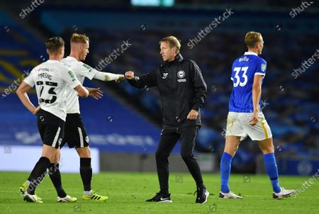 Brighton's head coach Graham Potter, center, salutes Portsmouth's players at the end of the English League Cup soccer match between Brighton and Portsmouth at Amex arena in Brighton, England