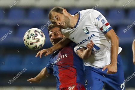 Basel's Valentin Stocker, left, jumps for the ball with Osijek's Mile Skoric during the Europa League second qualifying round soccer match between Osijek and Basel at the Gradski Vrt stadium in Osijek, Croatia