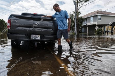 Brent Sexton walks back to his truck on a road flooded by Hurricane Sally after checking on his brother's home in Gulf Shores, Alabama USA on 17 September 2020. Hurricane Sally, which made landfall on 16 September as a Category 2 hurricane, brought damaging winds leaving most residents without power.