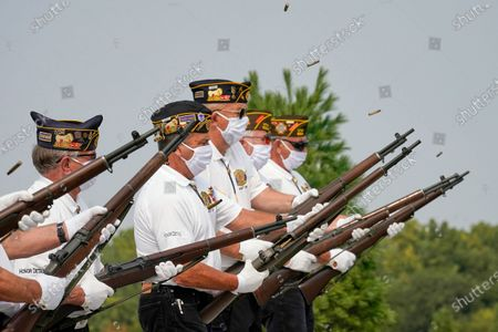 An honor guard with the American Legion Post 374 of Millard wear face masks against Covid-19 as they fire a three-volley salute during the graveside service of David Owen Cary at the Omaha National Cemetery in Omaha, Neb