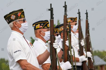 Stock Picture of An honor guard with the American Legion Post 374 of Millard wear face masks against COVID-19 present arms during the graveside service of David Owen Cary at the Omaha National Cemetery in Omaha, Neb