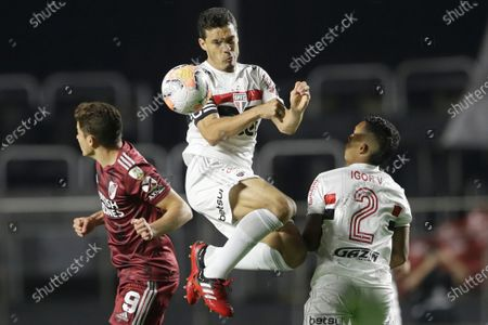 Stock Photo of Hernanes of Brazil's Sao Paulo foes for a header between his teammates Igor Vinicius, right, and Julián Alvarez of Argentina's River Plate during a Copa Libertadores Group D soccer match at the Morumbi stadium in Sao Paulo, Brazil