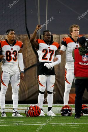 """Cincinnati Bengals cornerback Tony Brown (27) raises his fist during the playing of """"Lift Every Voice"""" by Alicia Keyes prior to the start of an NFL football game against the Cleveland Browns, in Cleveland"""