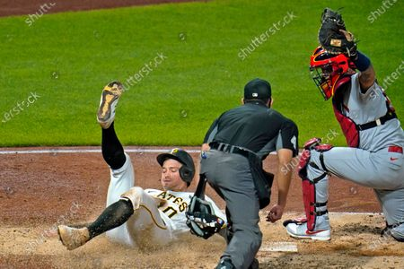 Stock Picture of Pittsburgh Pirates' Bryan Reynolds, left, is tagged out by St. Louis Cardinals catcher Yadier Molina, right, with umpire Robert Ortiz making the call during the sixth inning of a baseball game in Pittsburgh, . Reynolds attempted to score from second on a single by Kevin Newman