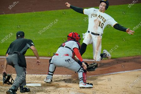 Pittsburgh Pirates' Bryan Reynolds (10) begins his slide before being tagged out by St. Louis Cardinals catcher Yadier Molina, center, with umpire Robert Ortiz making the call during the sixth inning of a baseball game in Pittsburgh, . Reynolds attempted to score from second on a single by Kevin Newman