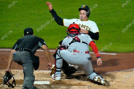 Pittsburgh Pirates' Bryan Reynolds, top, is tagged out by St. Louis Cardinals catcher Yadier Molina, center, with umpire Robert Ortiz making the call during the sixth inning of a baseball game in Pittsburgh, . Reynolds attempted to score from second on a single by Kevin Newman