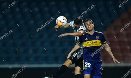 Leonardo Jara of Argentina's Boca Juniors, right, and Adrian Martinez of Paraguay's Libertad battle for the ball during a Copa Libertadores soccer match in Asuncion, Paraguay