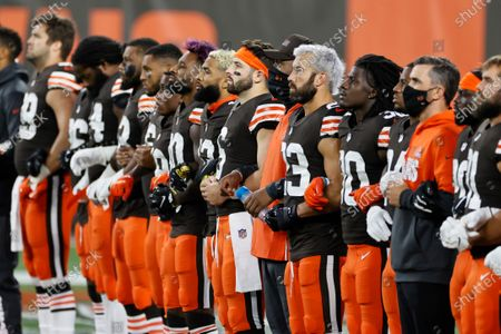 The Cleveland Browns line up arm-in-arm before an NFL football game against the Cincinnati Bengals, in Cleveland