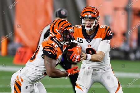 Cincinnati Bengals quarterback Joe Burrow, right, hands the ball off to running back Joe Mixon during the first half of the team's NFL football game against the Cleveland Browns, in Cleveland