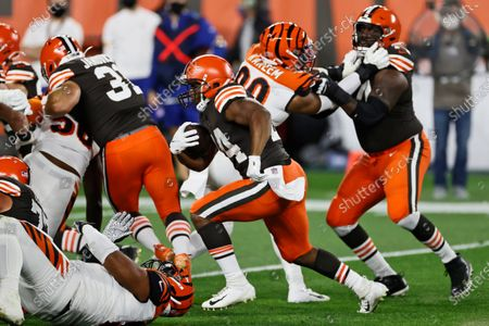 Cleveland Browns running back Nick Chubb, center, rushes for an 11-yard touchdown during the first half of the team's NFL football game against the Cincinnati Bengals, in Cleveland