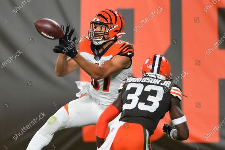 Cincinnati Bengals tight end C.J. Uzomah catches a touchdown pass next to Cleveland Browns' Ronnie Harrison Jr. during the first half of an NFL football game, in Cleveland