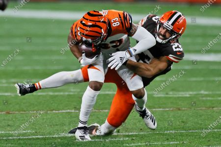 Cleveland Browns strong safety Andrew Sendejo (23) tackles Cincinnati Bengals wide receiver Tyler Boyd (83) after a pass reception during the second half of an NFL football game, in Cleveland