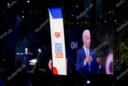 Democratic presidential candidate former Vice President Joe Biden, left, participates in a CNN drive-in town hall moderated by Anderson Cooper in Moosic, Pa., . At right Biden's image is projected onto a video monitor