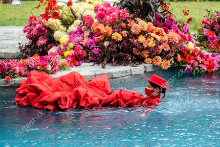Model Coco Rocha swims in a pool during the Christian Siriano fashion show held at Christian's home as part of New York Fashion Week on in Westport, Conn