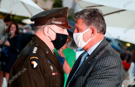 Stock Image of General Mark A. Milley, left, talks with Sen. Joe Manchin (D-WV), right, at the opening of the Dwight D Eisenhower Memorial, honoring the legacy of the World War II Supreme Allied Commander and nation's 34th President