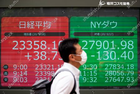 Man walks by screens showing Japan's Nikkei 225 index, left, and the Dow Jones Industrial Average, right, at a securities firm in Tokyo on . Asian shares were slightly higher Friday despite some investor attention shifting again to the uncertainties in global economies amid the coronavirus pandemic, as reflected in the overnight fall on Wall Street