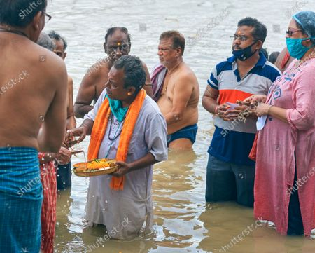 """A group of Hindu devotees to take part in the """"Tarpan"""" rituals, at Ganges embankment. A Hindu priests is helping them to perform the ritual. Tarpan is generally held in Pitru Paksha, which is is fortnight-long Hindu ritual marked annually, to pay homage to departed souls and ancestors. Though it was advised to wear face mask and maintain social distancing regarding coronavirus pandemic, only one of them is wearing face mask."""
