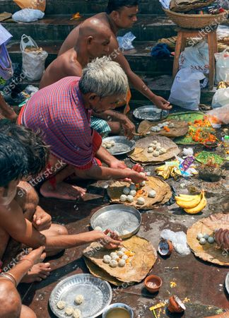 """Hindu devotees taking part in the """"Tarpan"""" rituals, at Ganges ghat. Tarpan are generally held in Pitru Paksha, which is is fortnight-long Hindu ritual marked annually, to pay homage to departed souls and ancestors. Though it was advised to wear face mask and maintain social distancing regarding coronavirus pandemic, it was not maintained during Tarpan."""