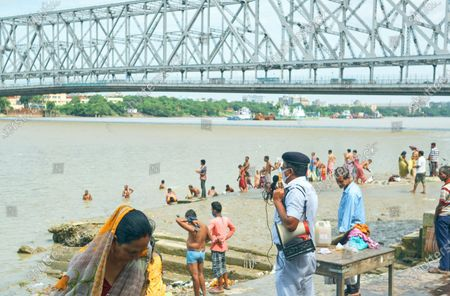 A Kolkata Police person wearing face mask  is seen in active duty during  gathering of Mahalaya Tarpan beside Ganges. He is holding a megaphone and alerting people not to go deep into the river while performing rituals. Iconic Howrah Bridge is seen in the background. Tarpan is generally held in Pitru Paksha, which is is fortnight-long Hindu ritual marked annually, to pay homage to departed souls and ancestors.