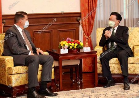 In this photo released by the Taiwan Ministry of Foreign Affairs, Taiwan's Foreign Minister Joseph Wu, right, meets with U.S. Undersecretary of State Keith Krach in Taipei, Taiwan on . China's military sent 18 planes including fighter jets over the Taiwan Strait in an unusually large show of force Monday as a U.S. envoy held a day of closed-door meetings on the self-governing island claimed by China