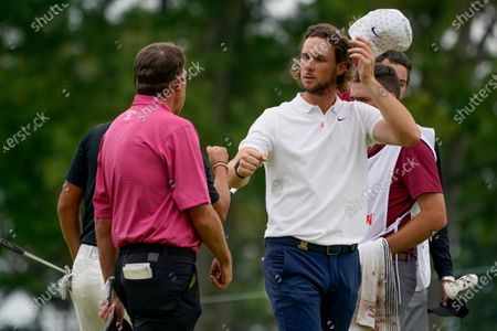 Thomas Pieters, of Belgium, bumps fists with John Pak and Jim Herman after finishing the second round of the US Open Golf Championship, in Mamaroneck, N.Y