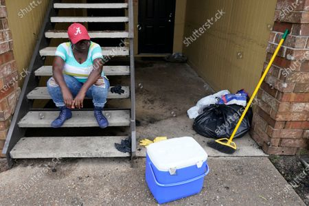 Karen Robinson takes a break after cleaning out her apartment in the aftermath of flooding after Hurricane Sally moved through, in, Fla