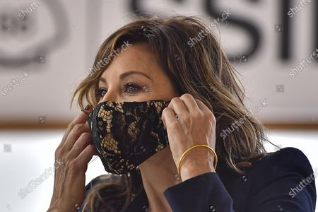 Actress Gina Gershon adjusts a face mask during a photo call to promote Woody Allen's film Rifkin's Festival during the 68th San Sebastian Film Festival, in San Sebastian, northern Spain