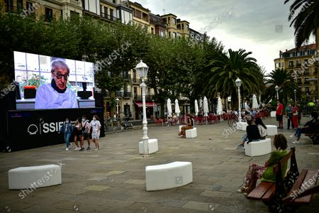 """People keep safe a distance in front of a giant screen as US film director Woody Allen takes part in a video conference press to promote his film """"Rifkin's Festival"""" during the 68th San Sebastian Film Festival, in San Sebastian, northern Spain"""