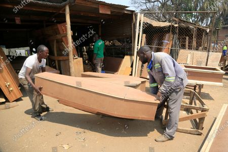 Stock Image of Vincent Nhidza (R) and colleague Mathew Simango (L) arrange coffins at a workshop in Mbare, Harare, Zimbabwe, 18 September 2020. Nhidza is a self taught carpenter who joined the informal sector after a forced early retirement. He is into coffin and casket making and he makes an average of one product per day or two days. The coffins and caskets range in price from 50 to 350 US dollar.