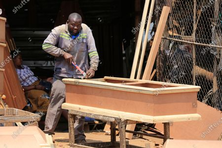 Vincent Nhidza makes a coffin at his workshop in Mbare, Harare, Zimbabwe, 18 September 2020. Nhidza is a self taught carpenter who joined the informal sector after a forced early retirement. He is into coffin and casket making and he makes an average of one product per day or two days. The coffins and caskets range in price from 50 to 350 US dollar.